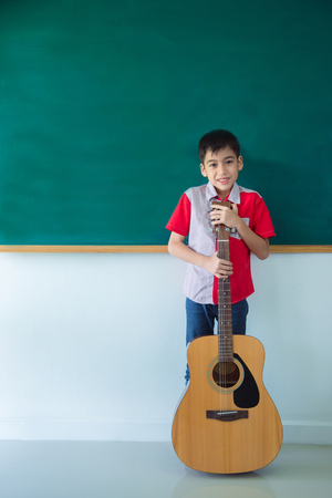 Young boy stading with guitar in front of blackboard in classroom