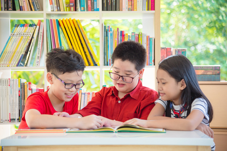 Three asian student reading book together in school library