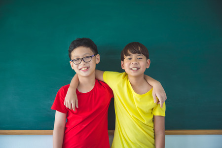 Two young asian student standing and smiling in front of chalkboard