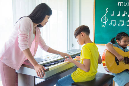 Young asian boy playing music keyboard with his teacher in classroom