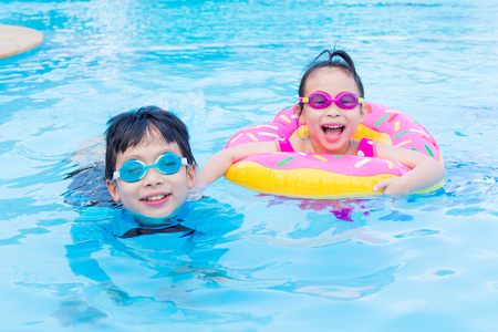 Little asian siblings happy together in swimming pool Stock Photo