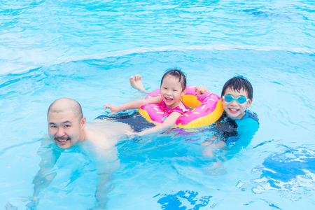 Happy Asian family playing together in swimming pool