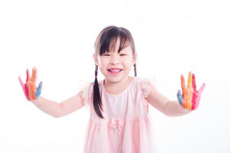Little asian happy girl showing painted hand over white background