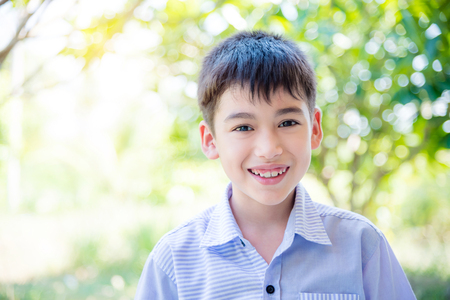 Young asian boy standing and smiling in park
