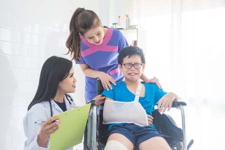 Beautiful asian doctor and nurse take care young boy patient who sitting and crying on wheel chair Stock Photo