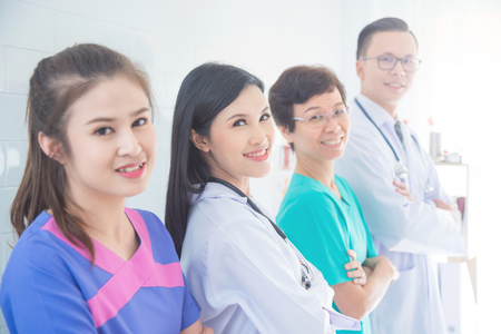 Attractive asian female doctor smiling in the row medical team group Stock Photo