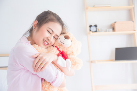 Young beautiful asian woman hugging teddy bear and smiles