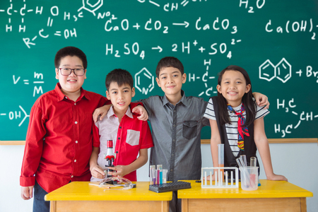 Group of Asian student standing and smile in front of chalkboard