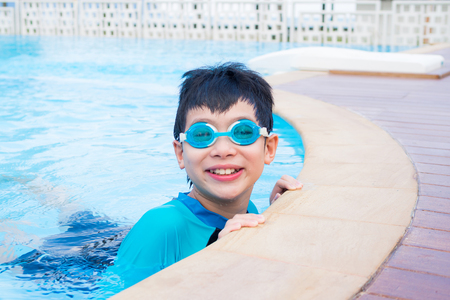 Young asian boy in swim suit smiling in swimming pool