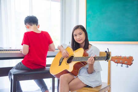 Beautiful girl playing guitar in classroom at school Stock Photo