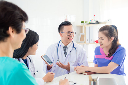 Group of doctors and nurses discuss and looking patients x-ray result in tablet computer Stock Photo