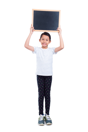 Young asian girl holding chalkboard and smiles over white background