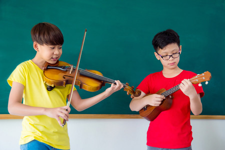 Young boys playing music instrument in classroom