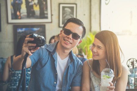 Young asian couple taking their photo by camera in coffee shop Stock Photo
