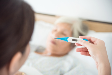 Nurse hand holding thermometer with high temperature result from senior female patient Stock Photo