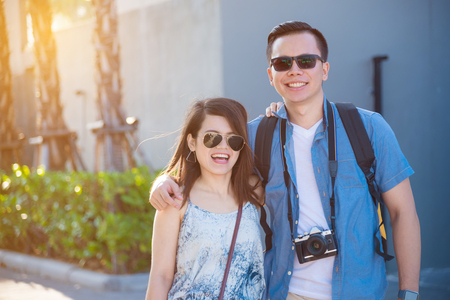 Young asian tourist couple smiling and walking on the street