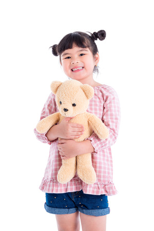 Little asian girl holding teddy bear and smiles over white background