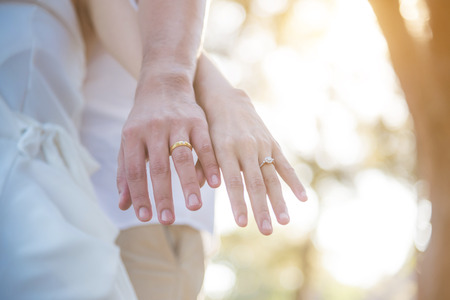 Couple hands with rings over sunset background Stock Photo