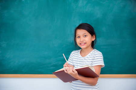 Young asian schoolgril reading book and smiling in front of chalkboard Stock Photo