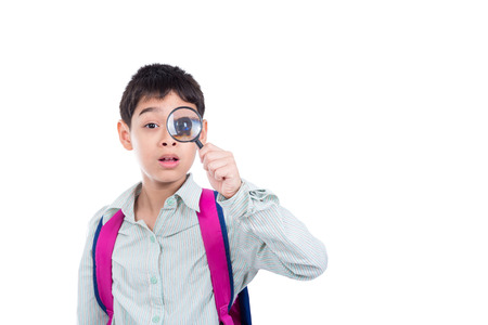 Young asian boy looking thru magnifying glass over white background