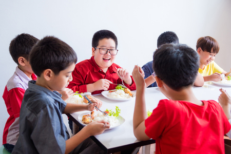 Asian schoolboy smiling while having lunch with friend at school canteen