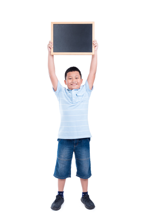 Young asian boy holding chalkboard and smiles over white background
