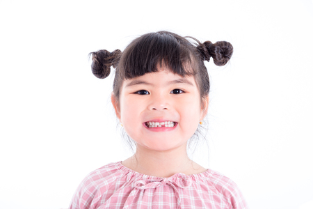 Little asian girl smiles and showing her first teeth lose over white background Stock Photo