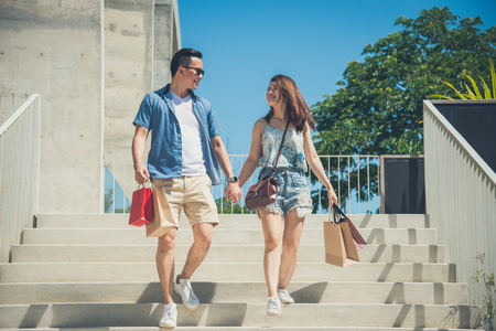 asian couple holding hand and smile while walking in shopping street