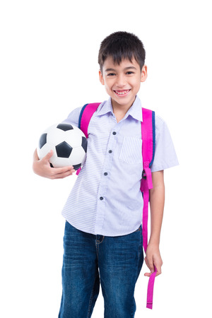 Young asian boy with backpack holding ball and smiles over white background