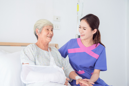 Senior asian female patient smiling with nurse who come to visit