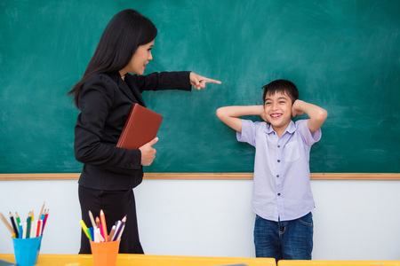 Asian schoolboy close his ears by hands and smiles while teacher scold him Stock Photo