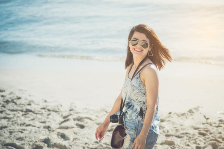 Beautiful asian woman traveller walking and smiles on the beach Stock Photo