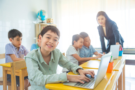 Young asian boy using laptop computer and smiles in classroom Stock Photo