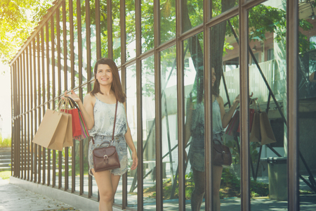 Beautiful asian woman holding many shopping bags and smiles while walking in shopping street Stock Photo