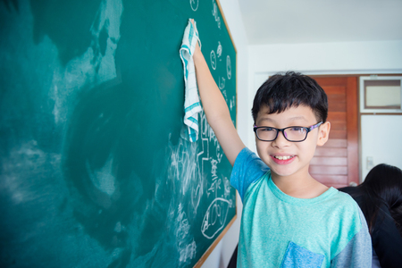 Young asian male student erasing chalkboard and smiles