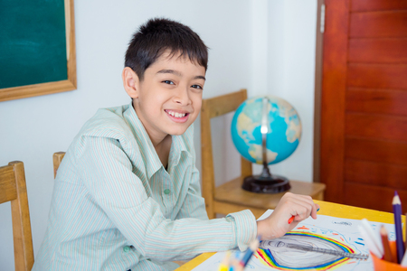 Young asian student sitting in classroom and smiling at camera