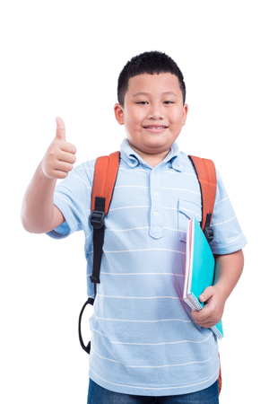 Young asian boy with backpack holding notebook and showing thumb up over white background