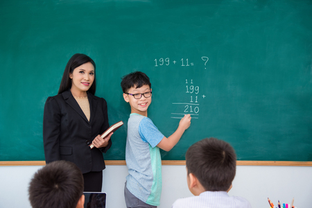 Young asian schoolboy writing answer on blackboard in classroom