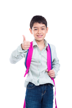 Young asian boy with backpack smiling and showing thumb up over white background