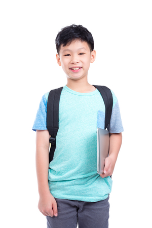Young asian boy with backpack holding notebook computer and smiles over white background Stock Photo