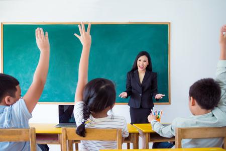 Belle enseignante asiatique enseignant aux élèves en classe