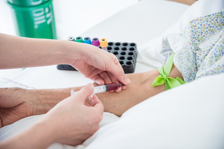 Nurse hands drawing blood from patient vein in hospital Stock Photo