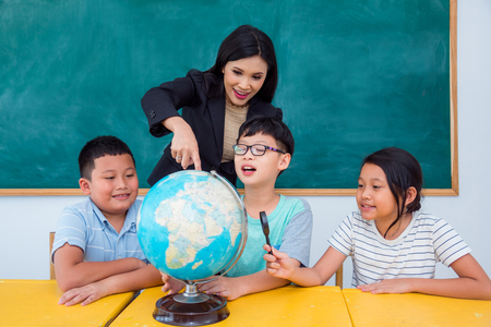Asian beautiful teacher and students studying geography in classroom Stock Photo