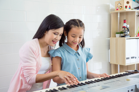 Asian beautiful teacher teaching student to play keyboard at school