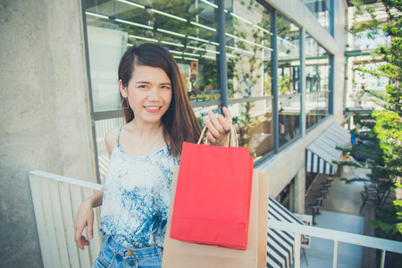 Beautiful asian woman holding many shopping bags and smiles