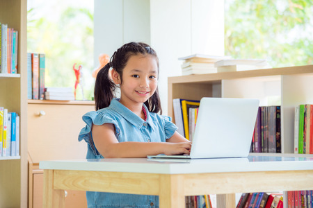Young asian girl using laptopcomputer in library Stock Photo