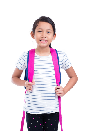 Young asian schoolgirl with backpack smiling over white backgroud Stock Photo