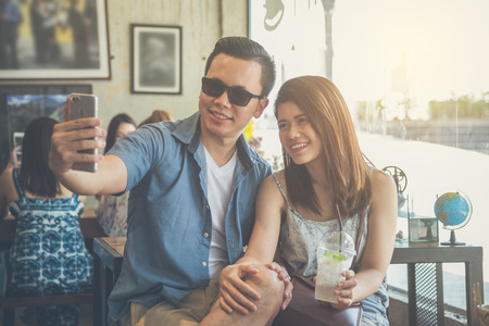 Young asian couple taking their photo by mobile phone in coffee shop Stock Photo