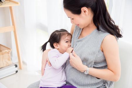 Weinig Aziatisch meisje consumptiemelk van haar zwangere moeder