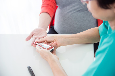 Nurse hands using glucometer to checking pregnant woman's blood sugar